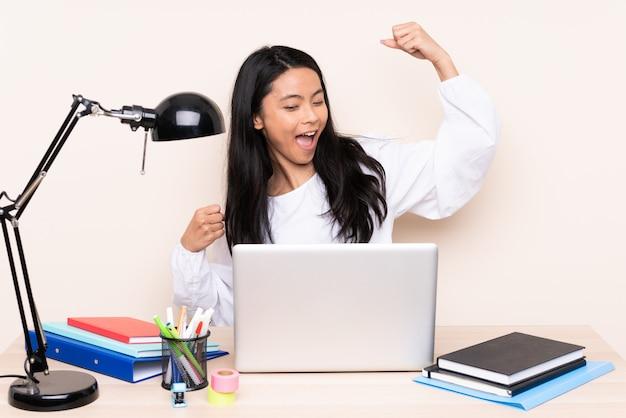 Studentenmeisje in een werkplaats met laptop op beige wordt geïsoleerd dat een overwinning viert die