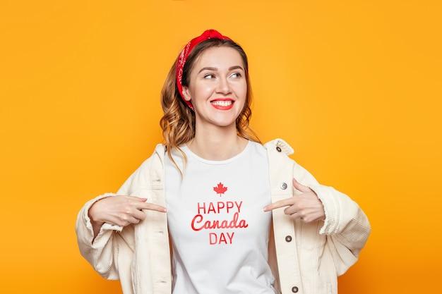 Studentenmeisje in een wit t-shirt wijst met een vinger naar de tekst happy canada day