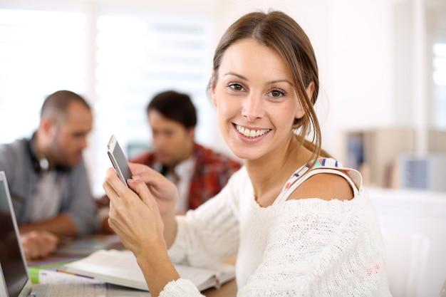 Studentenmeisje in klasse die smartphone gebruiken