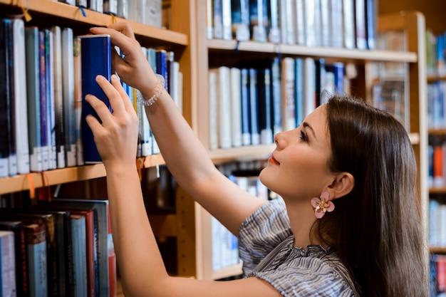 Studentenmeisje in kleding die noodzakelijk boek van de plank nemen