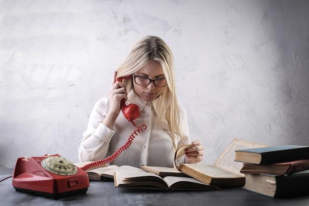 Studentenmeisje met een rode klassieke telefoon