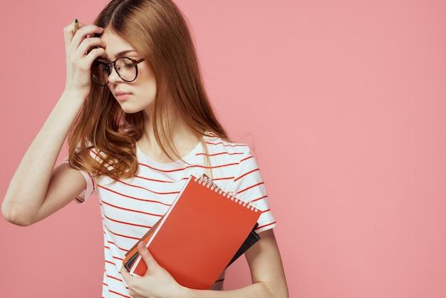 Studentenmeisje met glazen die met haar universiteitsboeken stellen