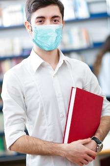 Studentenportret dat een masker, coronavirusconcept draagt
