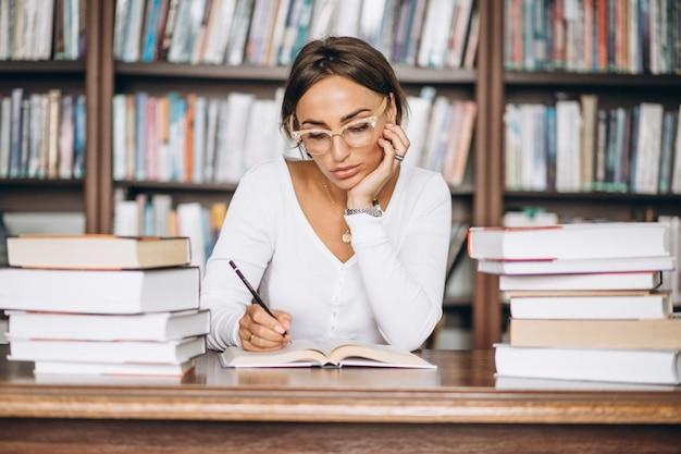 Studentenvrouw die bij de bibliotheek bestuderen