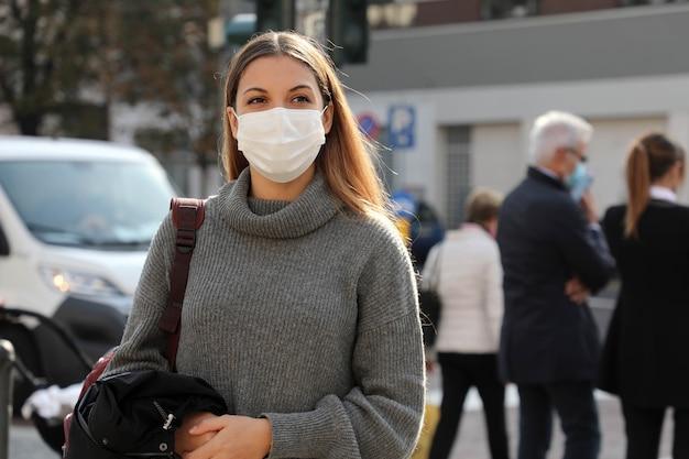 Studentenvrouw die in stadsstraat lopen die chirurgisch masker dragen. meisje met gezichtsmasker loopt op weg met mensen en verkeersauto's op de achtergrond.