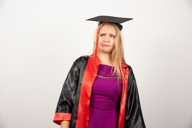 Studentenvrouw die in toga dwaas gezicht op wit maken.