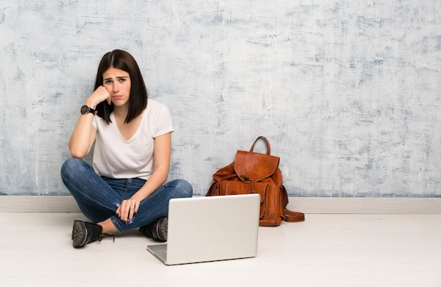 Studentenvrouw zittend op de vloer met droevige en depressieve uitdrukking