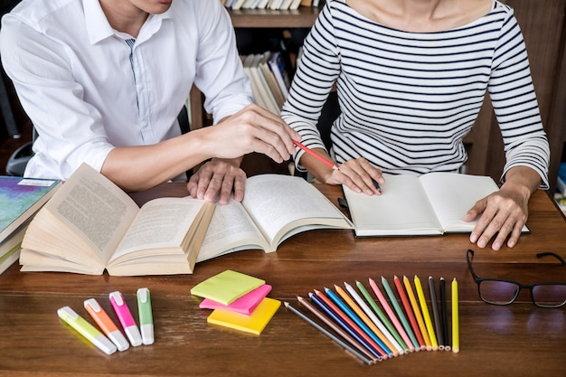 Studentenzitting in en bibliotheek die, thuiswerk en lessenpraktijk bestuderen die examen voorbereiden bestuderen