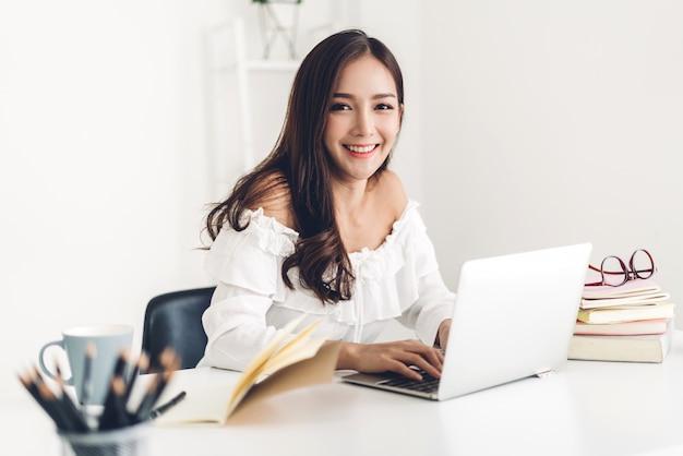 Studentezitting en het bestuderen en online het leren met laptop computer en het lezen van een boek vóór het examen thuis. onderwijsconcept