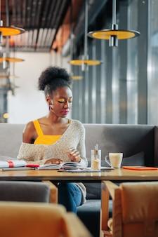 Studeren en drinken stijlvolle ijverige student die zich druk voelt tijdens het studeren en koffie drinken