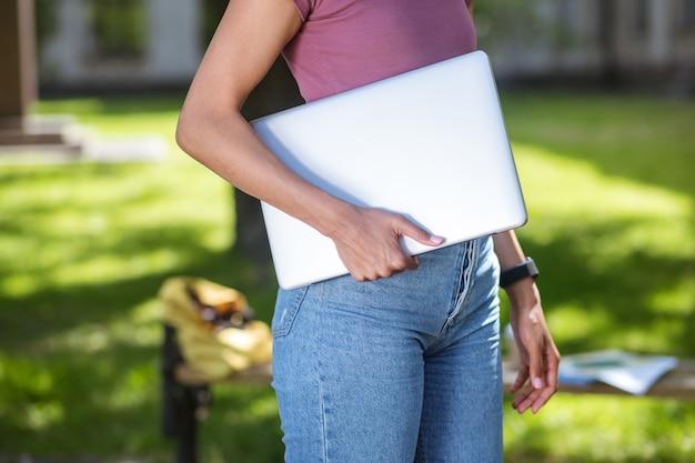 Studeren in het park. een meisje in een roze t-shirt met een laptop in het park