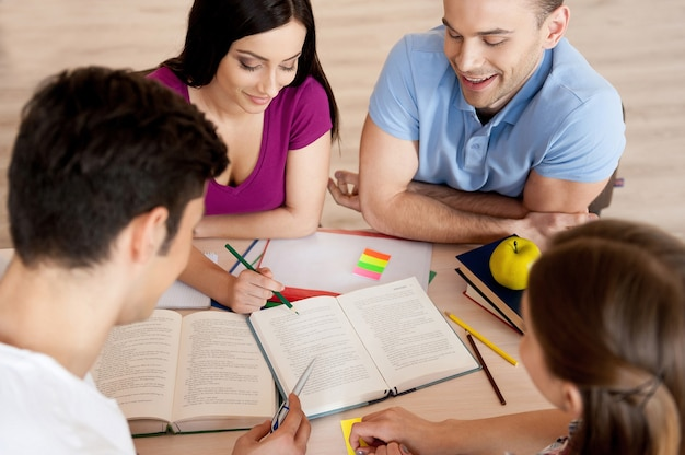 Studeren is leuk. bovenaanzicht van vier zelfverzekerde studenten die studeren terwijl ze samen aan het bureau zitten