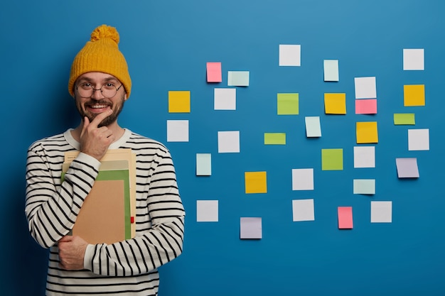 Studeren, leren en onderwijsconcept. vrolijke mannelijke student houdt kin, glimlacht gelukkig, staat met notitieboekje en leerboek, gekleed in modieuze kleding, maakt gebruik van plaknotities op blauwe muur