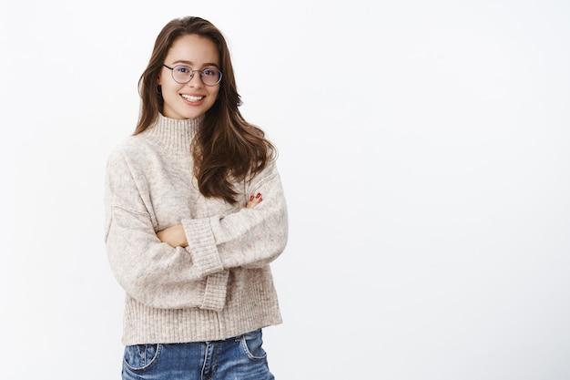 Studi shot van stijlvolle creatieve en gelukkige jonge europese vrouw in glazen met perfecte glimlach hand in hand gekruist over borst in zelfverzekerde vrolijke pose, warme trui dragend in koude winterdag.