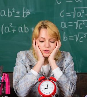 Studie en onderwijs. moderne school. kennis dag. terug naar school. leraren dag. school. thuisonderwijs. vermoeide vrouw. vrouw in de klas. leraar met wekker op blackboard. tijd. te vroeg.