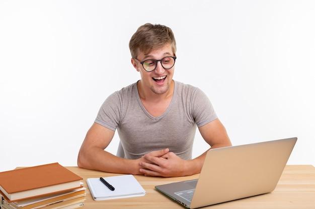 Studie, onderwijs en emoties concept. mannelijke student die oefeningen in laptop doet.