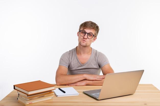 Studie, onderwijs en emoties concept. mannelijke student doet oefeningen in laptop, verbaasd kijkend.