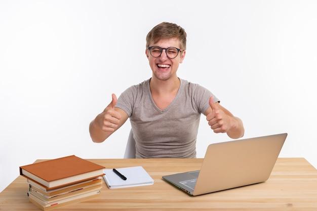Studie-, onderwijs- en emotiesconcept - mannelijke student die oefeningen in laptop doet, verbaasd kijkt