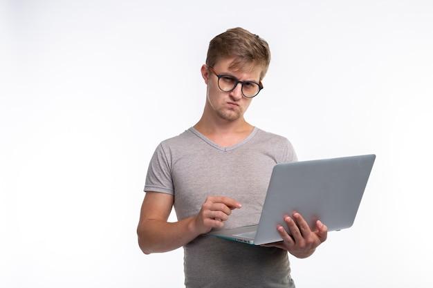 Studie, onderwijs en mensen concept. een serieuze jonge knappe man kijkt naar netbook op een witte achtergrond.