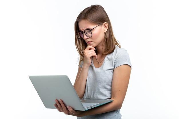 Studie, onderwijs, mensen concept - jonge slimme vrouw in glazen texting iets op laptop
