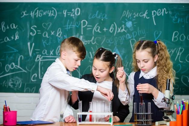 Studie van vloeibare toestanden. groepsschoolleerlingen met reageerbuisjes bestuderen chemische vloeistoffen. school laboratorium. meisjes en jongen die experimenteren met vloeistoffen. reageerbuisjes met kleurrijke vloeibare stoffen.