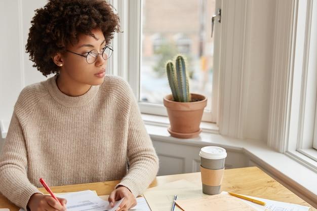 Studieonderwijs, werkconcept. nadenkende vrouwelijke bankier vult documentatie in, houdt pen vast