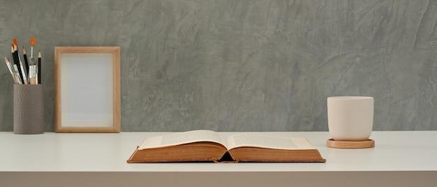 Studietafel met geopende boekbeker briefpapier en mock-up frame