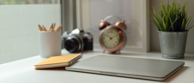 Studietafel met gesloten laptop, notebook, briefpapier, camera, klok en decoraties op witte tafel