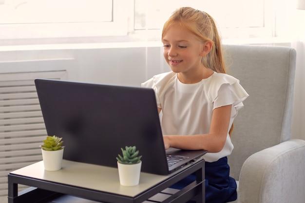 Studietijd een geïnteresseerd klein schoolmeisje zit en kijkt naar een educatieve videoles