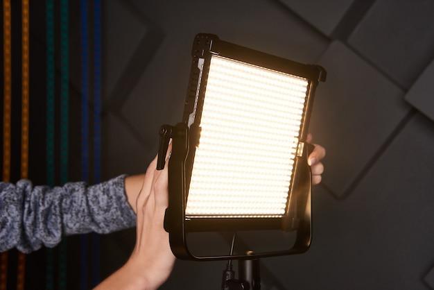 Studio-assistent bevestigt professionele videolamp op verstelbare lichtstatief