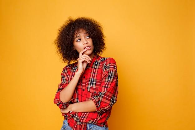 Studio beeld van het denken van mooie jonge afrikaanse vrouw poseren geïsoleerd op oranje achtergrond gekleed in rood shirt.