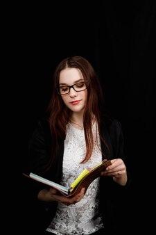 Studio close-up portret van een meisje van slavische verschijning versleten zwarte jas en bril op een zwarte achtergrond met bruin notitieboekje in haar handen.