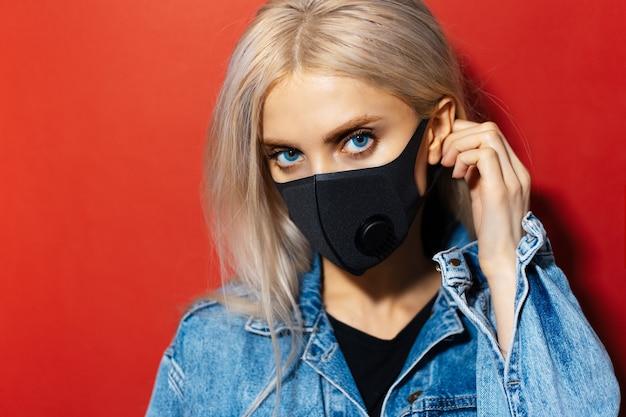 Studio close-up portret van jong blond meisje met blauwe ogen, ademhalingsmasker van zwarte kleur dragen, tegen coronavirus. achtergrond van rode kleur met exemplaarruimte.