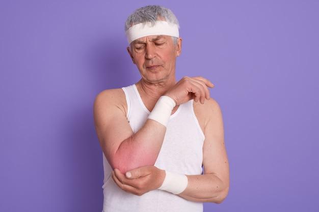 Studio die van bejaarde is ontsproten die witte mouwloze t-shirt en hoofdband draagt