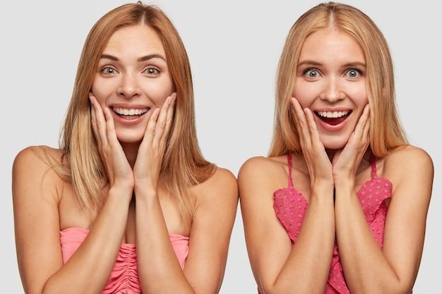 Studio die van blije twee jonge vrouwen met lang licht haar is ontsproten, handen op wangen houden, brede glimlachen hebben