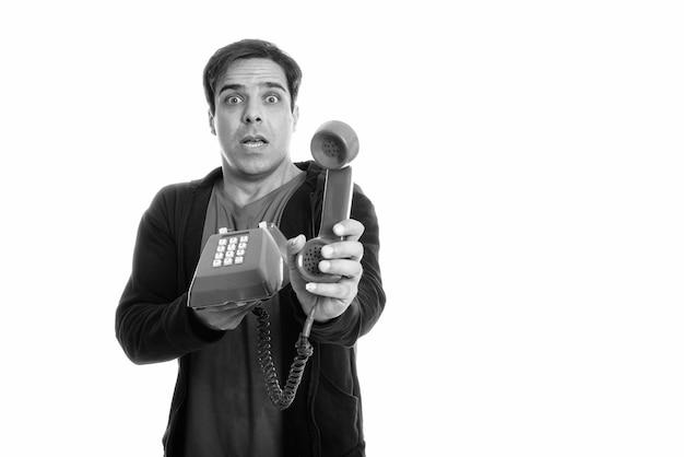 Studio die van de jonge perzische mens is ontsproten die geschokt kijkt terwijl het geven van oude geïsoleerde telefoon