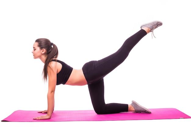 Studio die van een jonge geschikte vrouw is ontsproten die yogaoefeningen doet die op witte achtergrond worden geïsoleerd