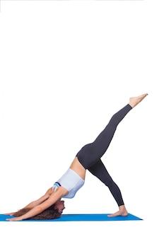 Studio die van een jonge geschikte vrouw is ontsproten die yogaoefeningen doet.