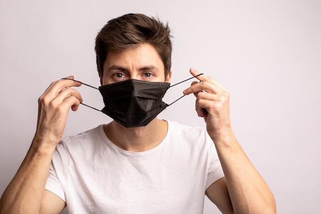 Studio die van een jonge mens is ontsproten die een zwart masker draagt, dat camera bekijkt, die op wit wordt geïsoleerd