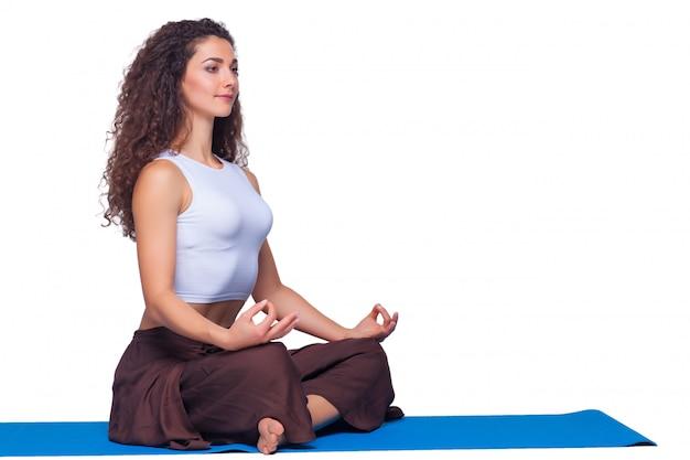 Studio die van een jonge vrouw is ontsproten die yogaoefeningen op witte achtergrond doet