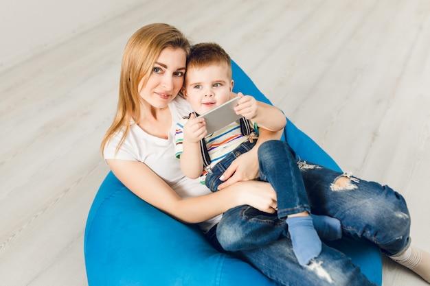 Studio die van een moeder is ontsproten die haar kind in wapens houdt. jongen speelt op smartphone en glimlacht