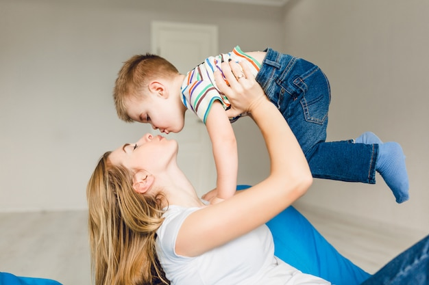 Studio die van een moeder is ontsproten die met haar kind speelt. moeder houdt jongen in haar armen