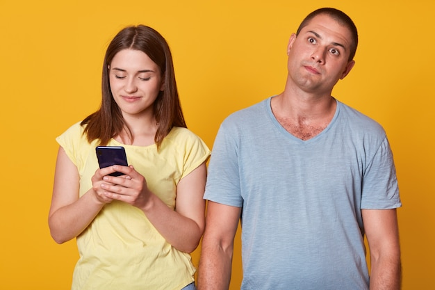 Studio die van jong paar, aantrekkelijk vrouwelijk texting bericht op smartphone is ontsproten, mannetje dat met nadenkende gelaatsuitdrukking omhoog kijkt