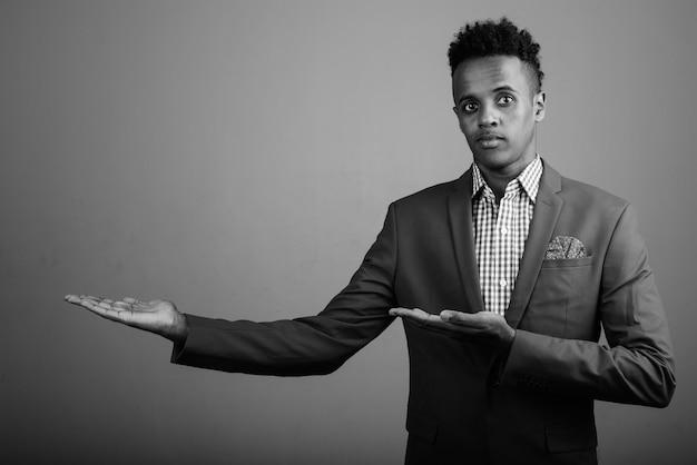 Studio die van jonge knappe afrikaanse zakenman is ontsproten die kostuum tegen grijs in zwart-wit draagt