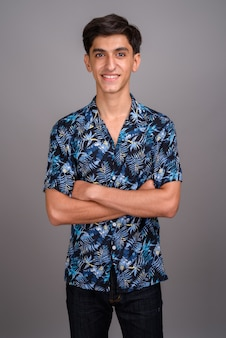 Studio die van jonge knappe perzische tiener is ontsproten die hawaiiaans overhemd draagt tegen grijze achtergrond