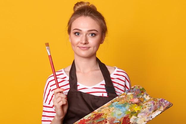Studio die van jonge mooie vrouw is ontsproten die wit toevallig overhemd met rode strepen draagt