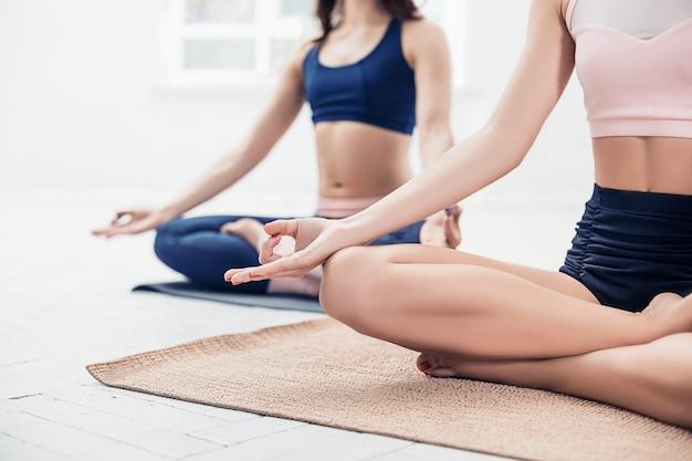 Studio die van jonge vrouwen is ontsproten die yogaoefeningen op wit doen