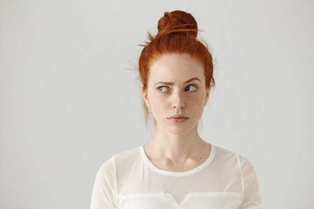 Studio die van leuk roodharig meisje met haarknoop en sproeten is ontsproten zijwaarts kijkt