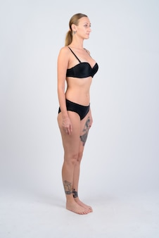 Studio die van toeristenvrouw met blond haar is ontsproten die bikini tegen wit draagt