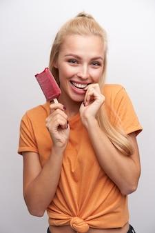 Studio foto van aantrekkelijke gelukkige jonge blonde vrouw met casual kapsel ijs in opgeheven hand houden en camera kijken met charmante glimlach, geïsoleerd op witte achtergrond